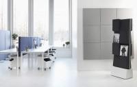 Na levé straně je modrá řada podlahových akustických paravánů. Mezi stoly jsou modré stolní akustické paravány. Šedé čtverce na stěně jsou nástěnné akustické moduly. To vše je SONEO.